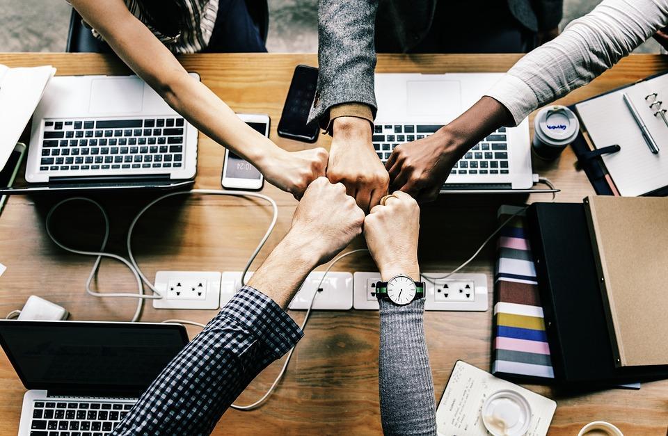 Sülearvutite kohal viie inimese käed keskele kokku pandud